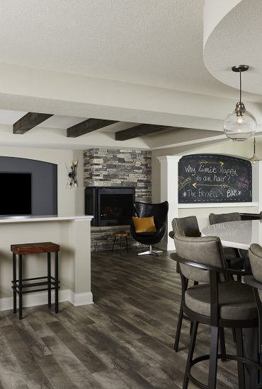 "A 42"" H drink ledge adds another lvel of seating for the family room. Luxury Cinyl Plank flooring will stand up to the biggest gatherings and still look great. Curved soffit detail at the bar features a rustic wood herringbone inset."