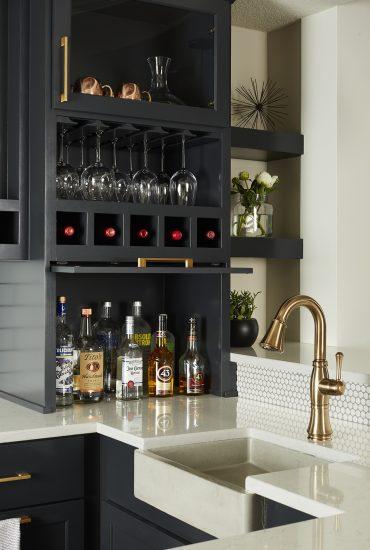 Farm sink, brushed brass faucet and hardware, dark enameled custom cabinet, wine racks, floating shelves, and penny round backsplash