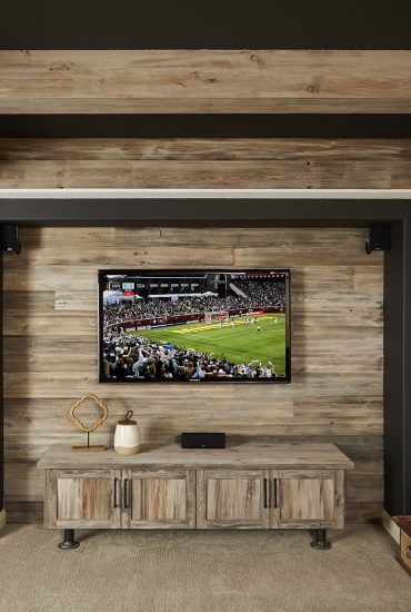 Dark painted ceiling and TV wall with rustic wood accents and beams.
