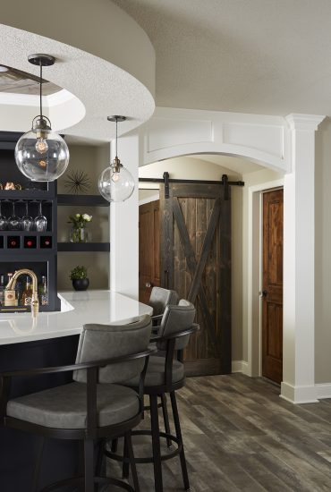 So many custom features in this basement. Sliding distressed wood barn door, curves, arches and white woodwork details.