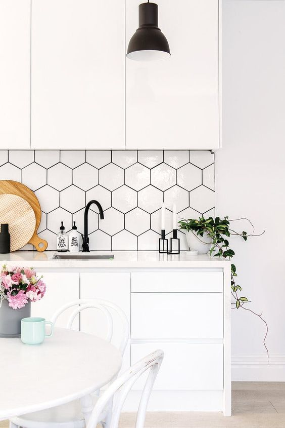 White monochrome kitchen with white hex tile backsplash and black faucet