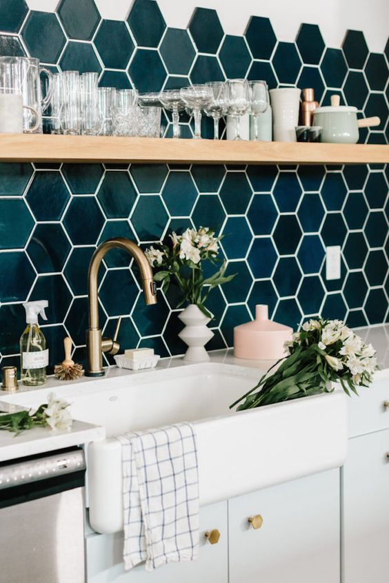 Green hex tile backsplash with brass faucet and open shelving