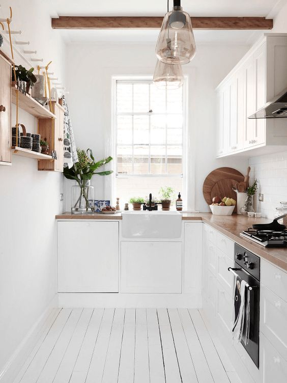 Butcher block countertops and wood accents add warmth to a white kitchen