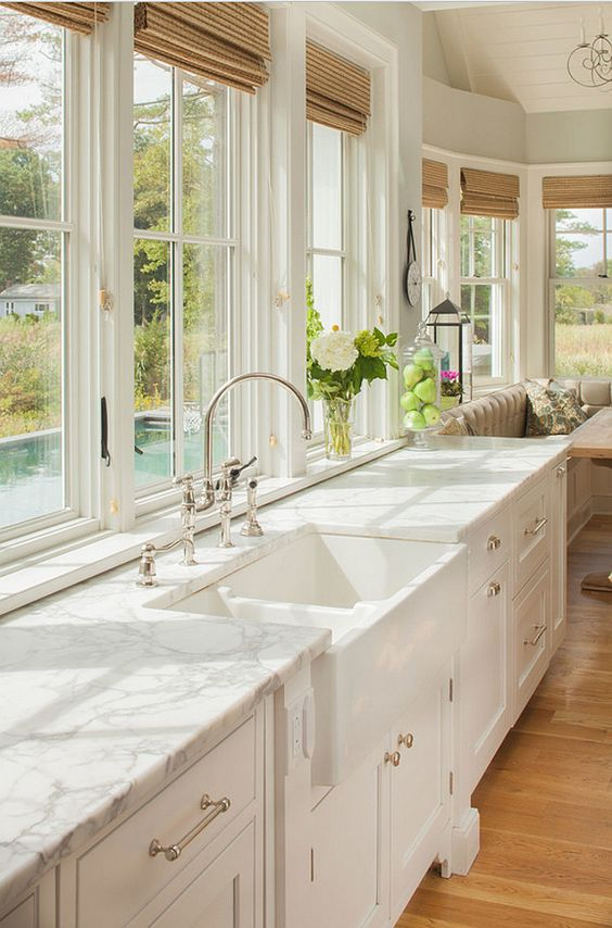 Natural woven window shades complement an all-white kitchen