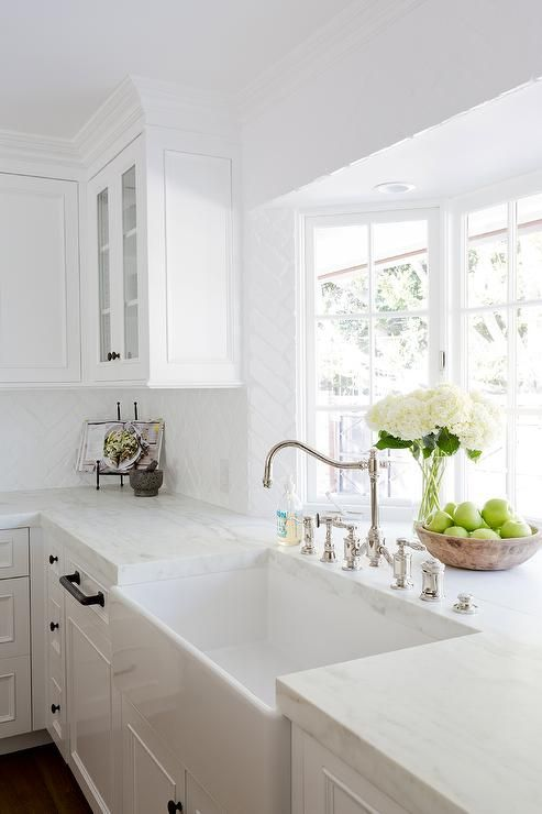A white porcelain sink makes for a streamlined look in a white kitchen