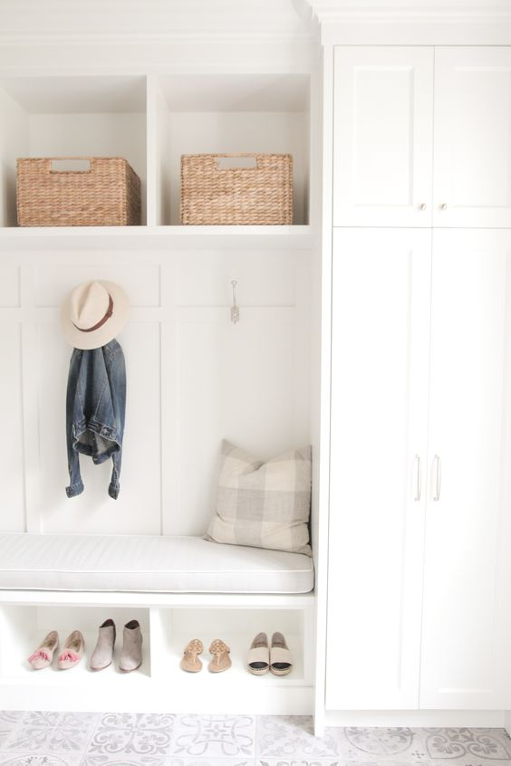 A sleek white mudroom invites the summer sun inside