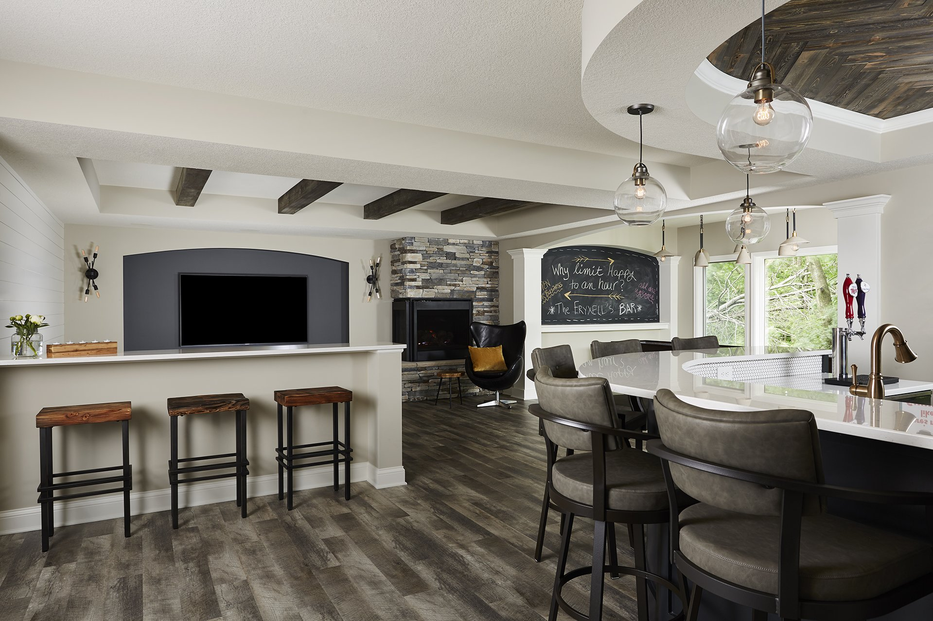 Dropped soffits above the basement bar and throughout the room provide architectural contrast and interest while simultaneously hiding dropped ductwork