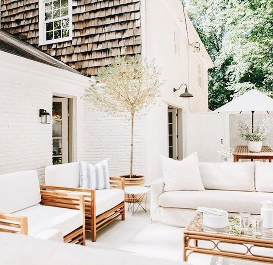 Bright white lounge seating pairs with wood elements for an inviting summer look
