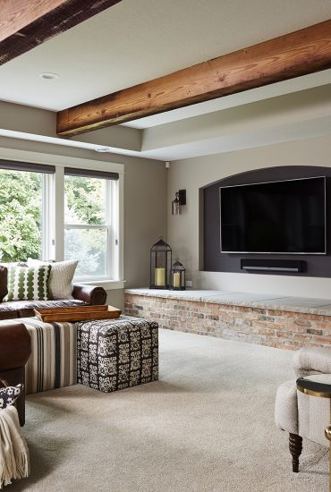 The lounge space in this new basement finish surrounds a combined TV/fireplace feature wall (with a two-sided fireplace) and rustic wood beams give movement and warmth to the ceiling, making the space feel open and airy – the ideal welcoming space for guests.