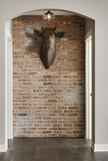 A mounted bull head adorns this exposed brick hallway wall, giving an eclectic and unique vibe to this remodeled basement.