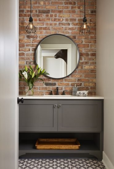 Exposed brick and graphic gray and white floor tiles surround a gray bathroom vanity to create a gorgeous blend of contemporary style.