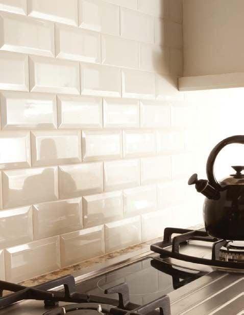 Kitchen backsplash uses cream beveled subway tiles for a sophisticated look