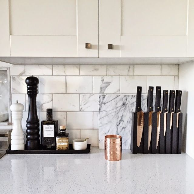 A white and bright kitchen with white and gray marbled subway tile