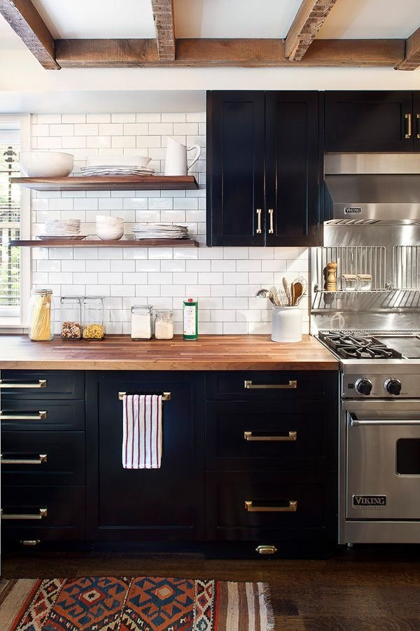 White subway tile backsplash pops against dark kitchen cabinets and butcher block counters