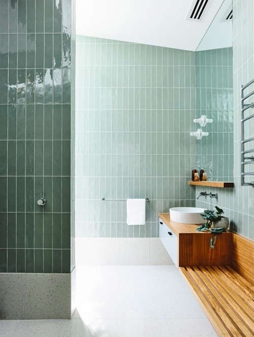 This bathroom uses sea foam green glass subway tiles for a subtle and chic color pop