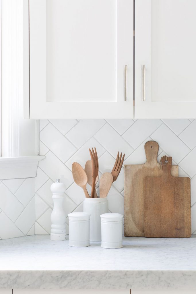 A unique kitchen backsplash with white subway tiles in a herringbone pattern