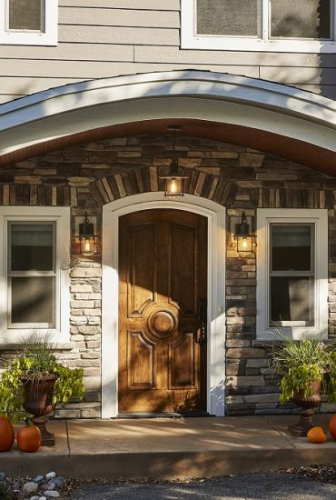 Front Entry with curved eyebrow style roof lines, new curved top wood front entry door, tapered columns and stone. All new exterior finshes.