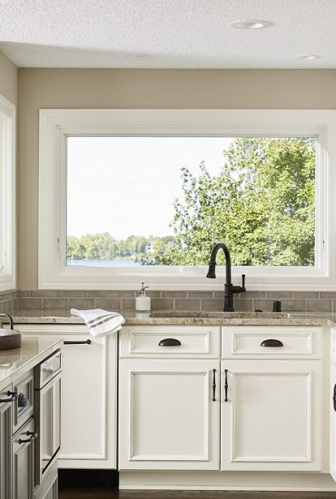 Kitchen sink view to lake. Creamy white cabinets and grey center island.