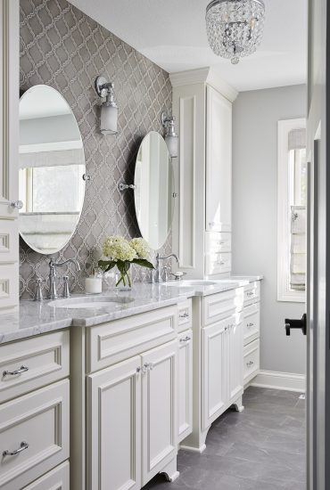 Custom vanity with leg detail in creamy white with a marble top. Chrome fixtures, and grey tile floor.