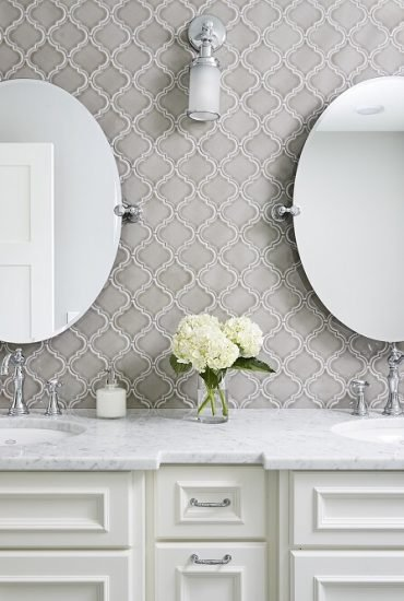 Grey arabesgue backsplash tile, creamy white custom vanity with cararra marble top. His and her sinks and sconce lighting.