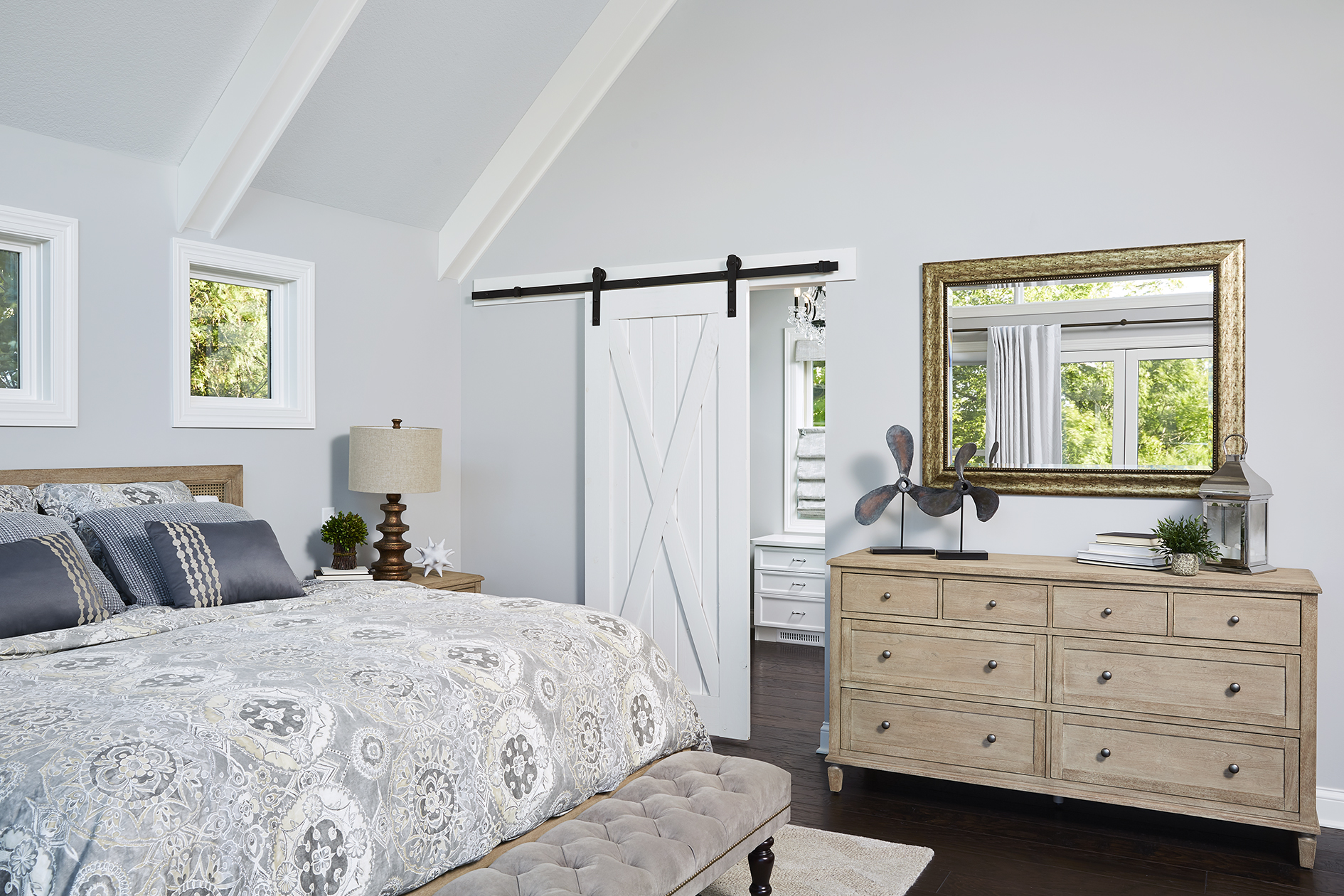 A classic sliding white barn door acts as the entrance to the walk-in closet, providing a unique visual element to the space and saving floor space.