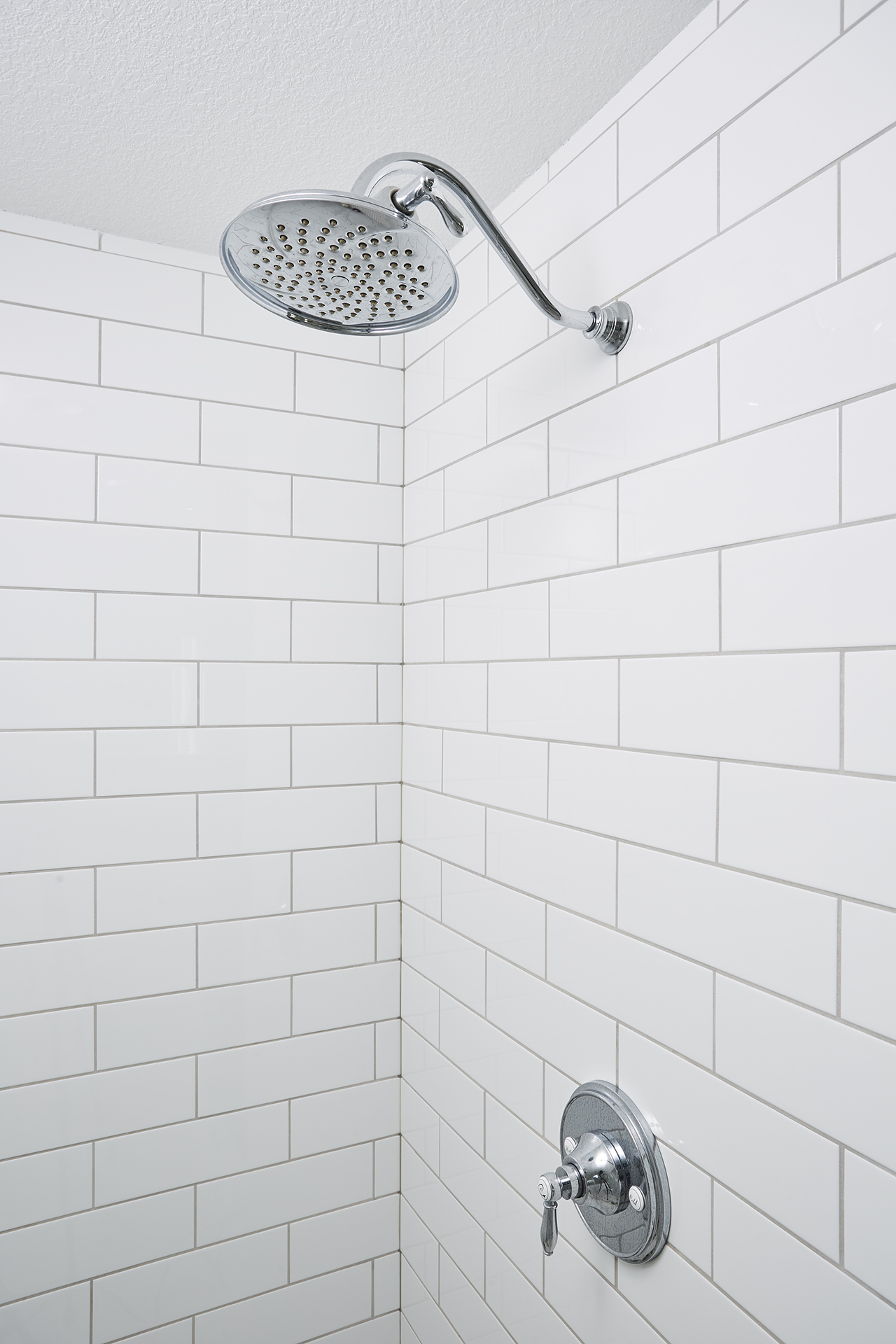 A chrome shower head adds a touch of shine and glamour to this bathroom, giving the space a feeling of luxury.