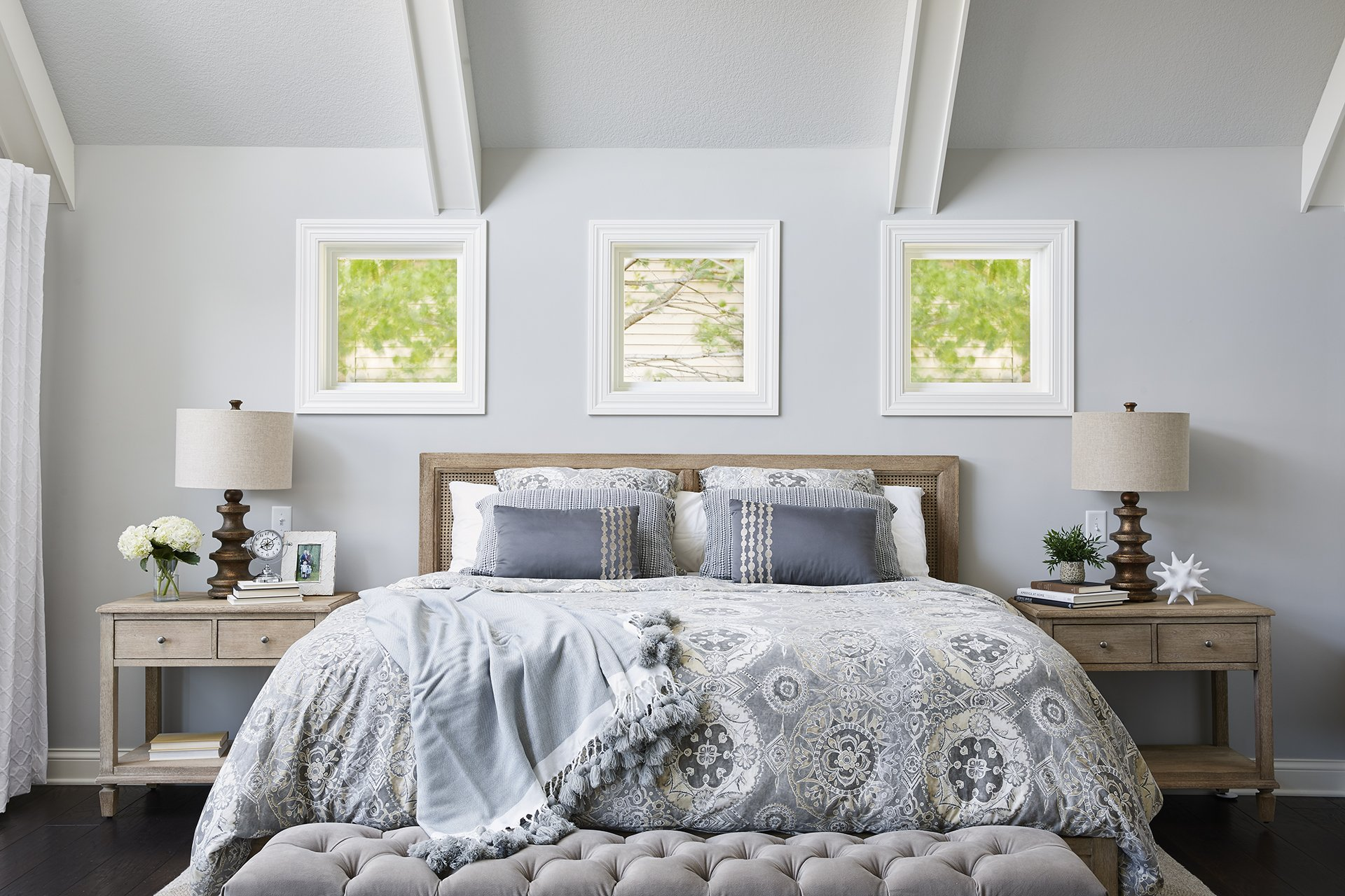 Soft shades of blue co-mingle in this patterned duvet, while a distressed wood headboard and dark finished lamps provide contrast, creating an inviting focal point for the space.