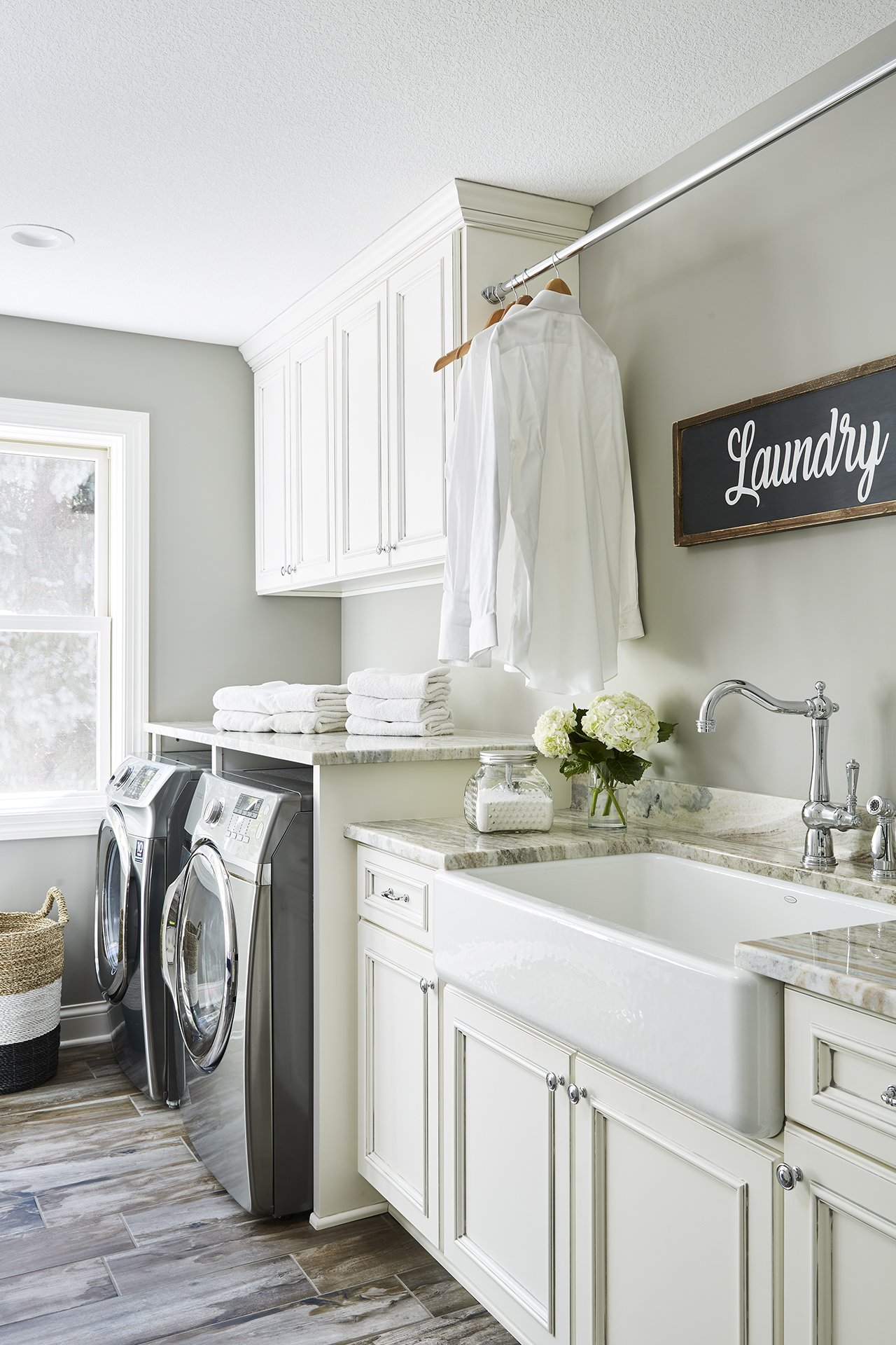 A white farmhouse apron sink gives this laundry room a classic touch, while creamy white cabinets contrast beautifully against wood grain-inspired floor tiles.