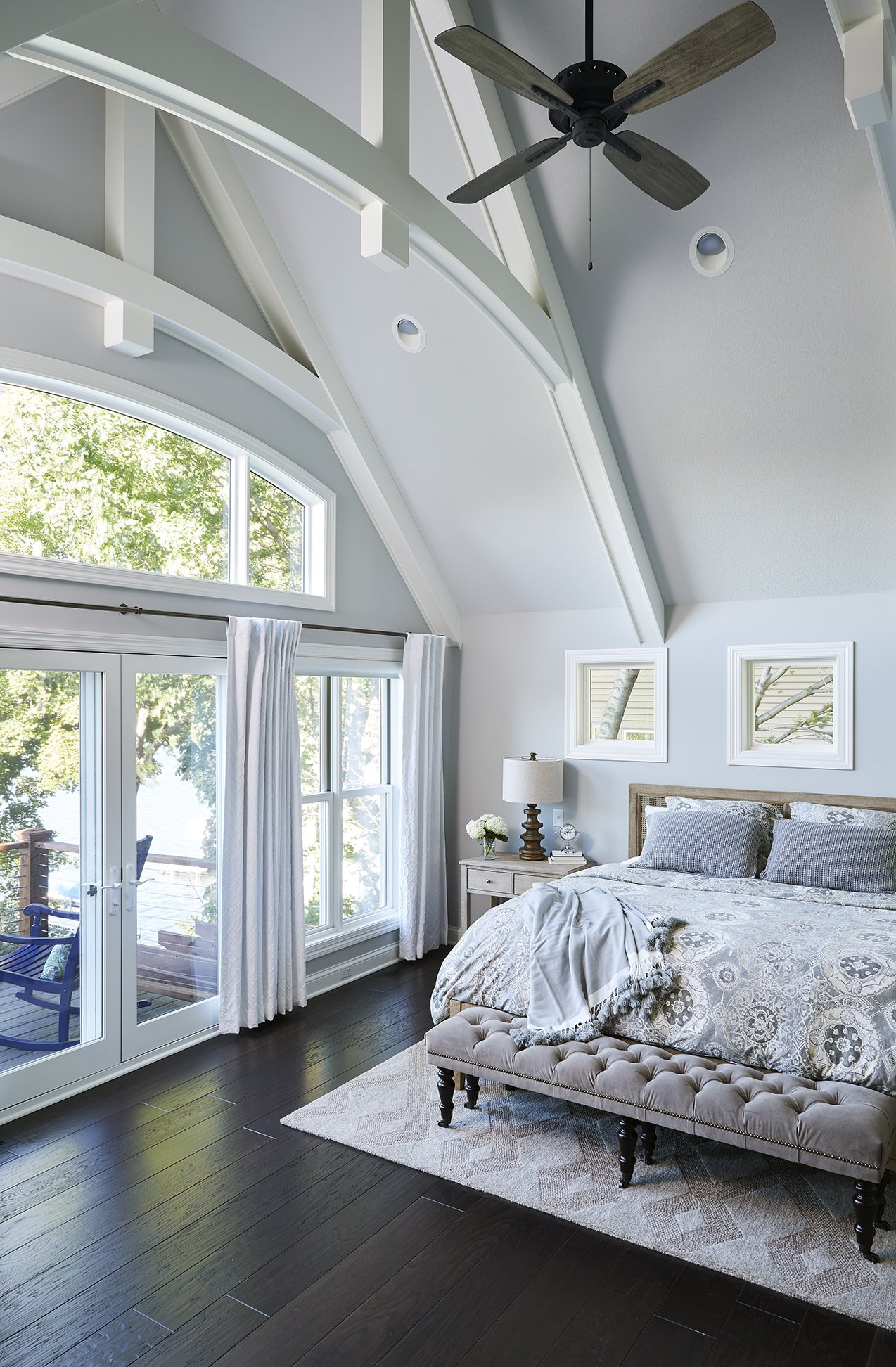 Floor-to-ceiling windows bring bright natural light into the space while ceiling beams add much-needed dimension and depth, accentuating the ceiling height and making this master bedroom the perfect place to relax.