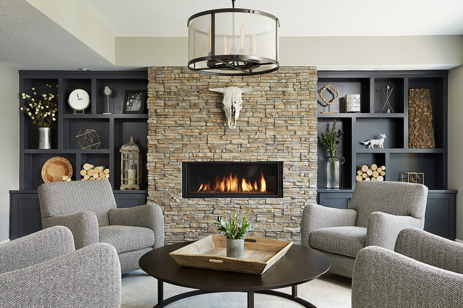 In this cozy basement, a fireplace feature wall takes center stage, filled with custom bookshelves that add architectural interest and sleek and high-quality armchairs that provide comfortable seating for guests.