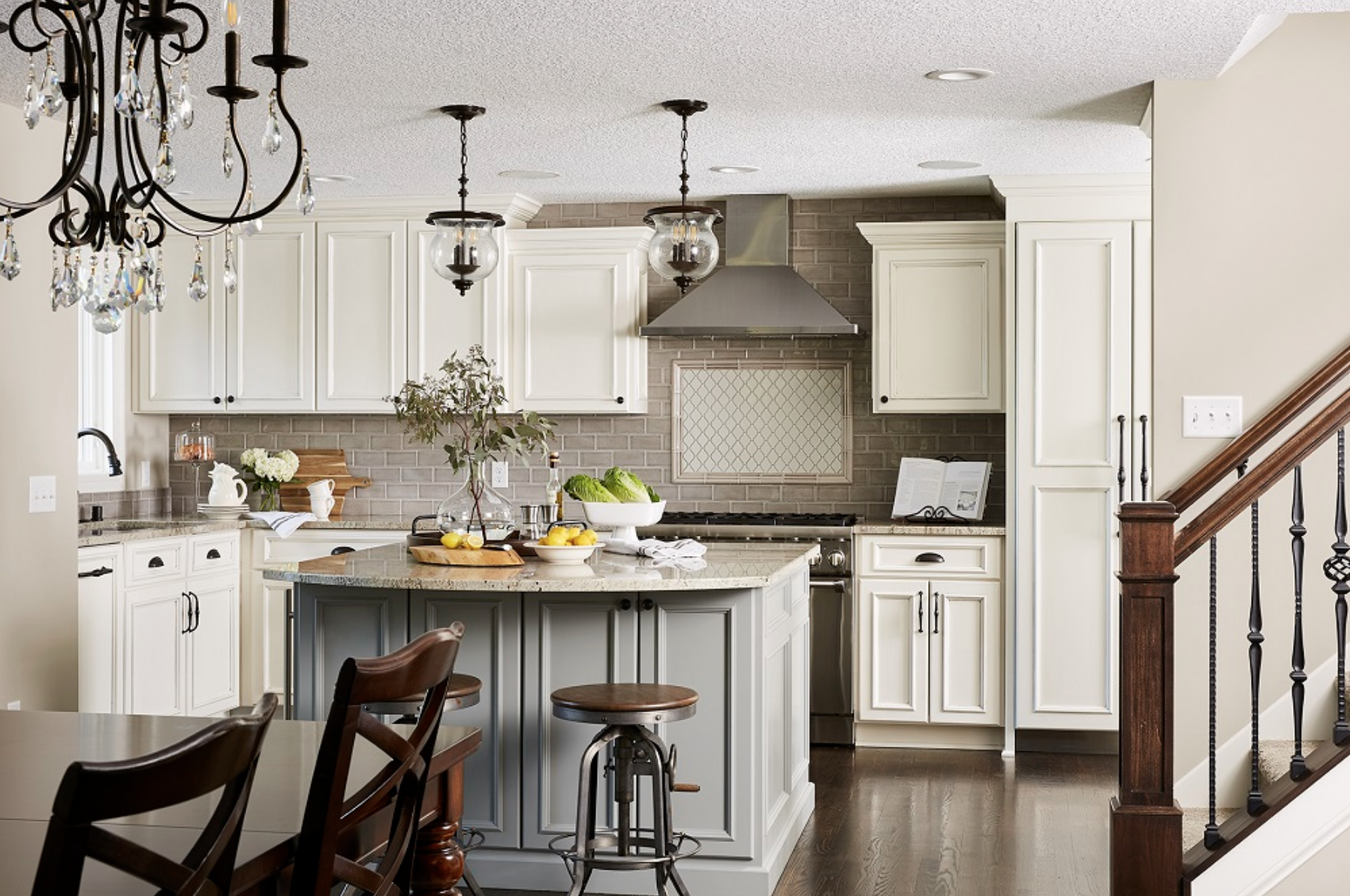 A soft grey kitchen island pulled a touch of coolness into this space, offering contrast to the warm white surrounding cabinets.