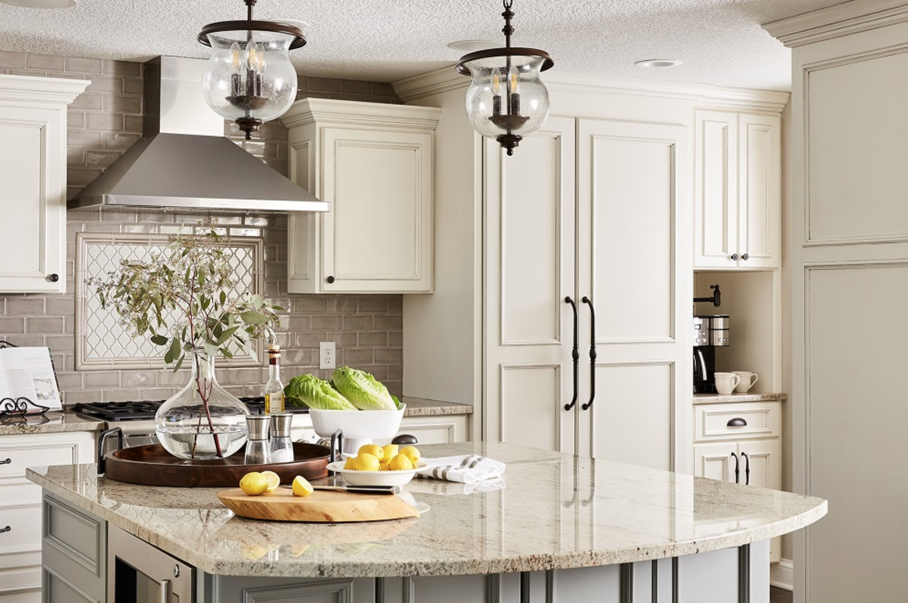 A hidden refrigerator was positioned behind custom cabinet panels, giving the kitchen a cohesive and bright white look.