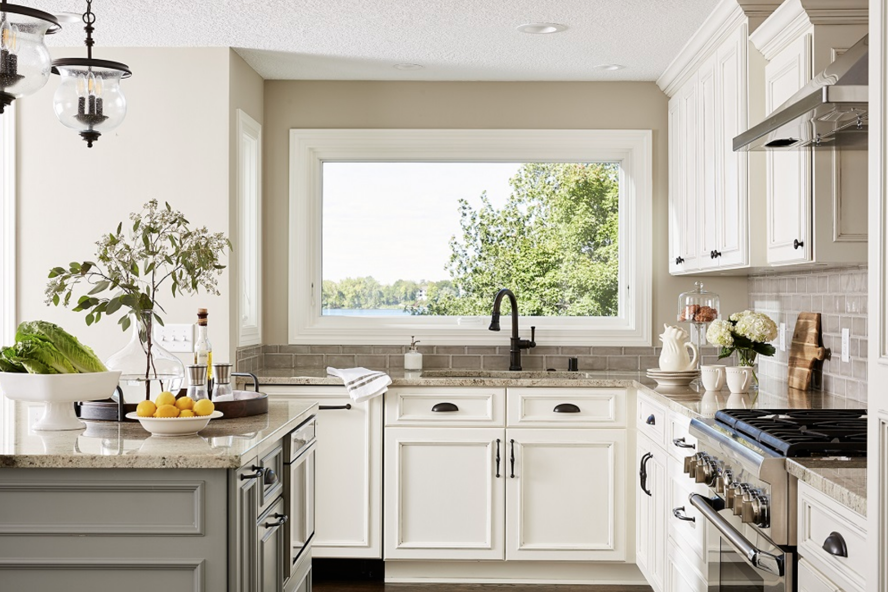 Touches of warm grey and soft white throughout this kitchen paired perfectly with the oil-rubbed bronze finishes for a streamlined and classic aesthetic.