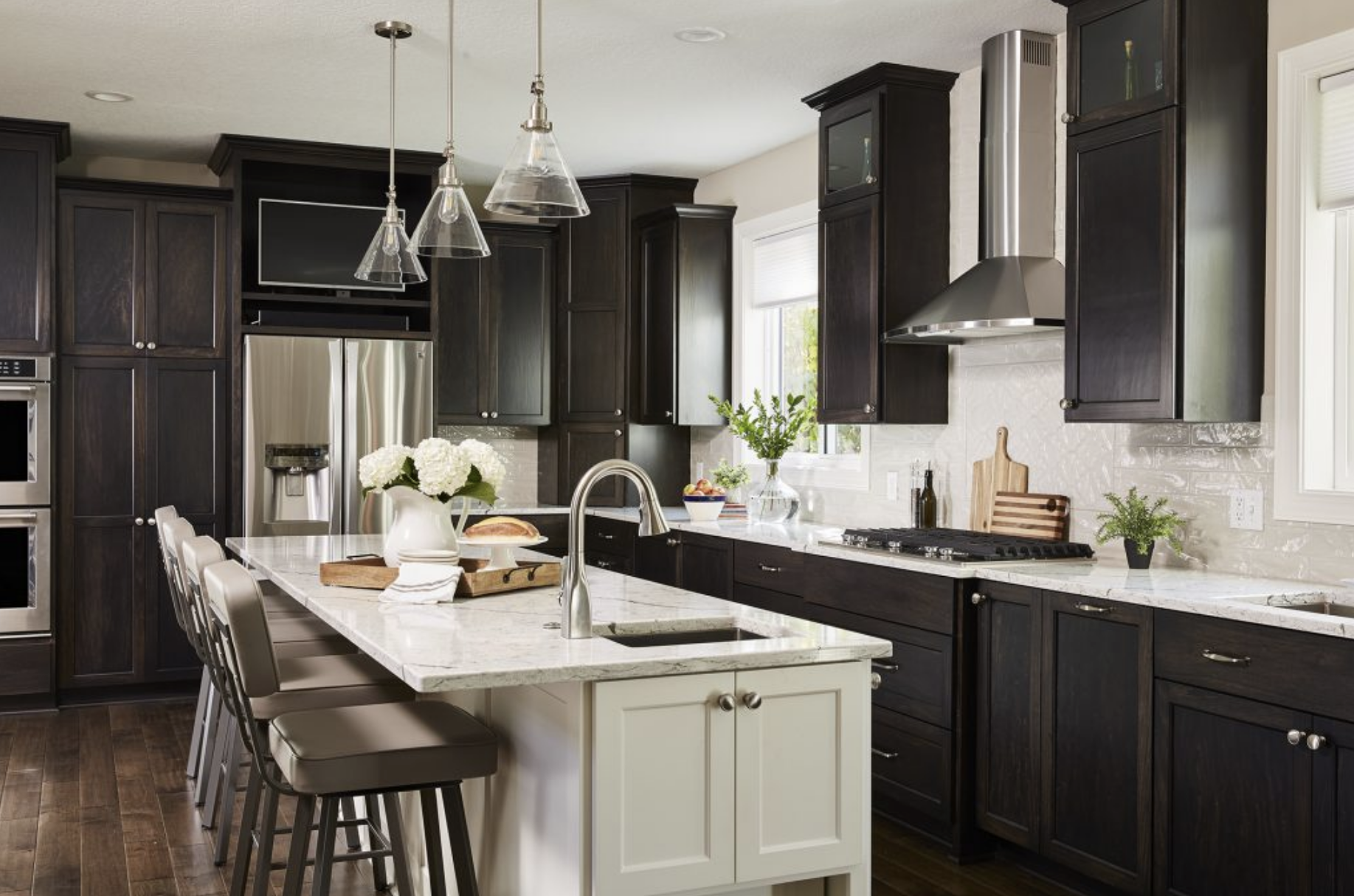 Rich, dark kitchen cabinets against a light backsplash and walls made for a sophisticated kitchen style in this home.