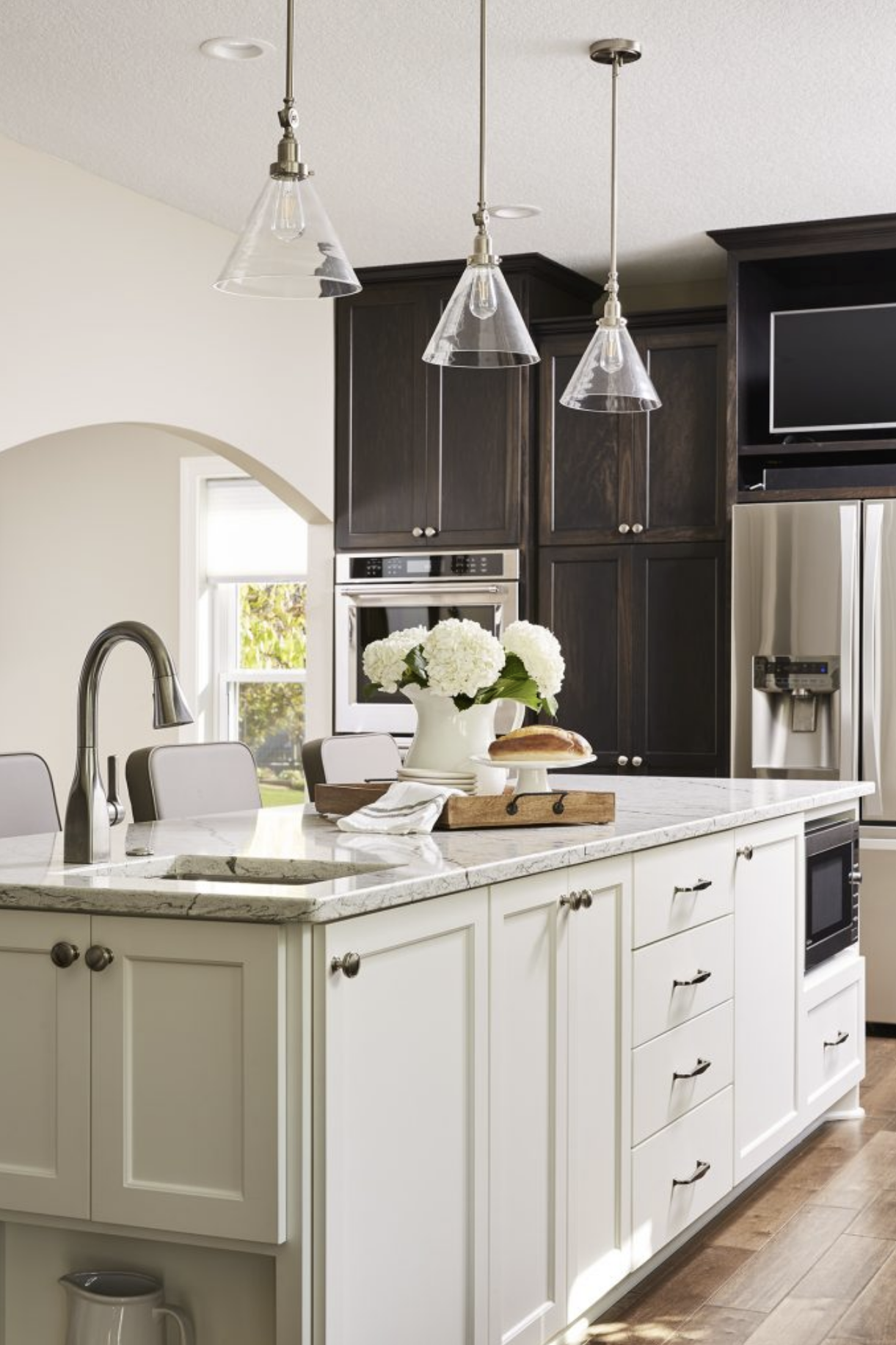 A white kitchen island with a light quartz countertop contrasted perfectly with the surrounding dark cabinets in this kitchen.