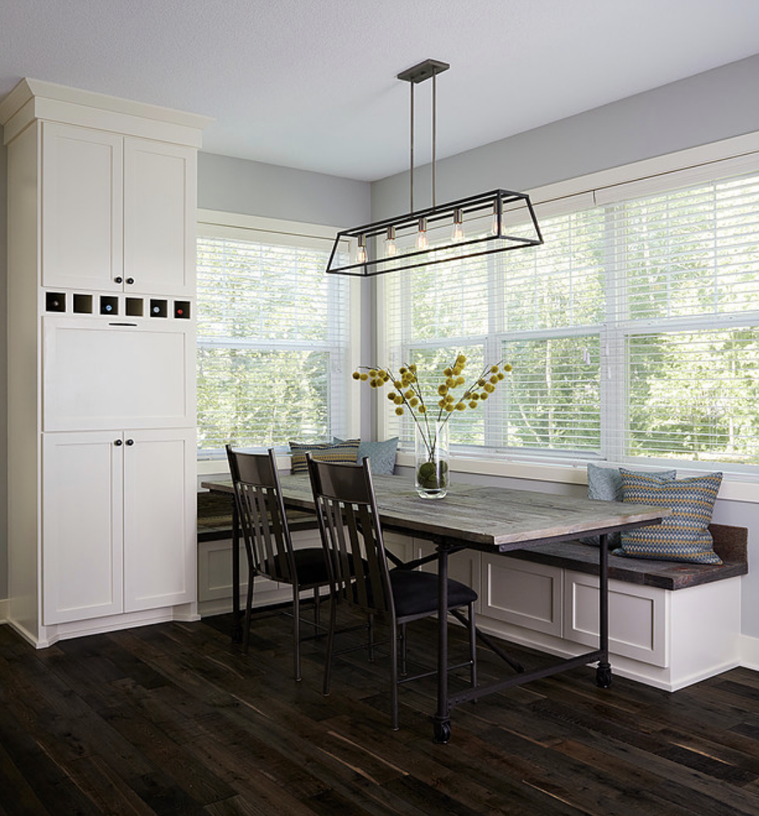 Reclaimed wood pops in the dining room table and built-in bench seating gave this kitchen a modern farmhouse aesthetic.