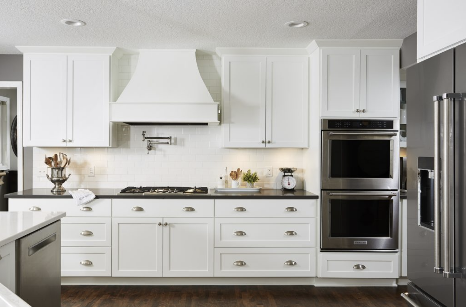 All-white cabinets and backsplash were paired perfectly with a sleek grey quartz countertop for a classic look in this open kitchen.