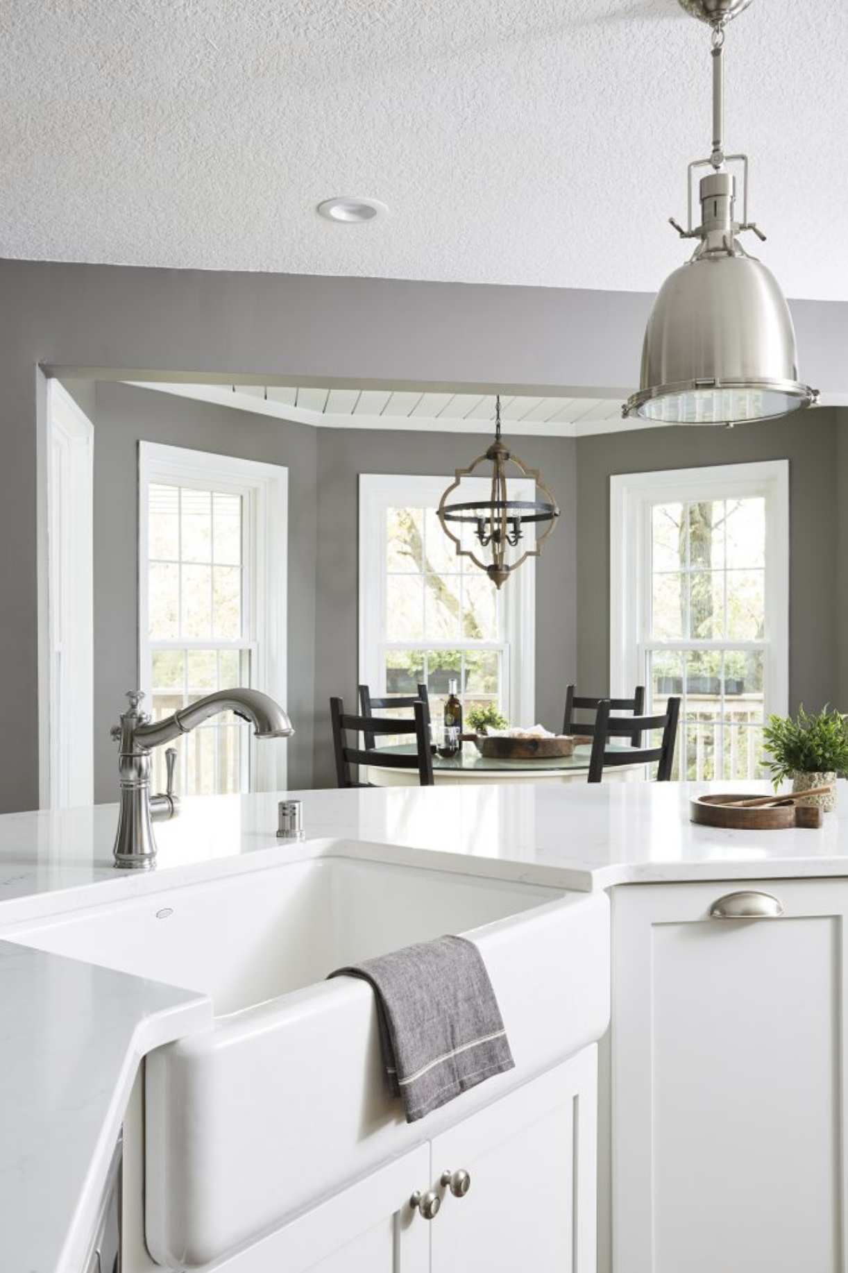 Bright white countertops were built around a farmhouse-style sink for a classic and timeless kitchen aesthetic.