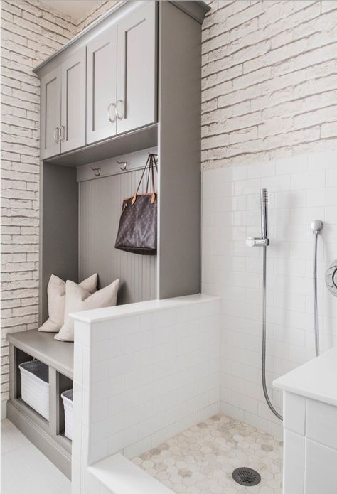 This beautiful grey and white mudroom includes a step-in shower station with surrounding walls to prevent splashing, and ample space for both pets and kids to clean up before entering the house. / Source