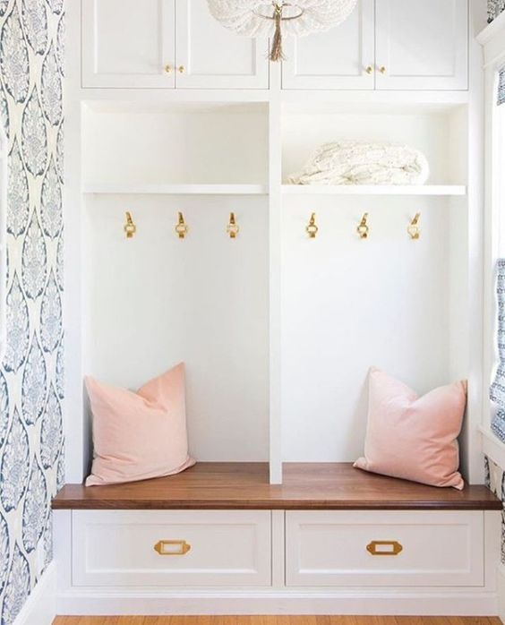 A pop of brass in this mudroom's hooks and drawer hardware pairs perfectly with its feminine splashes of pink and whimsical wallpaper pattern. / Source