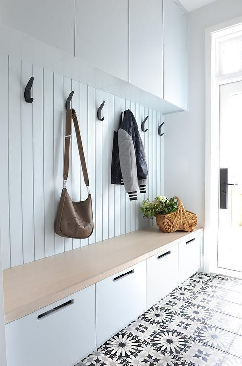 In this mudroom, simple black hooks are evenly spaced to allow for ample storage space for coats, bags, and more. / Source