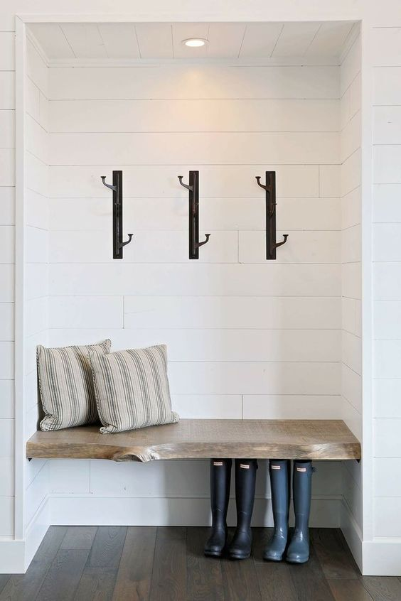Modern and chic black iron hooks are both functional and stylish in this neutral mudroom space. / Source