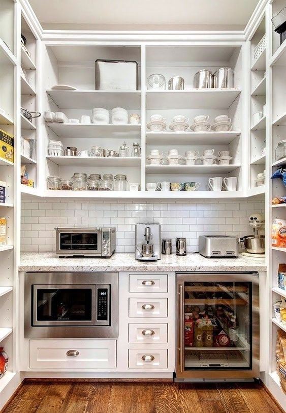 This butler's pantry keeps the microwave, toaster, mixer, and espresso machine all in one place, leaving the main kitchen with beautiful open and spacious countertops.