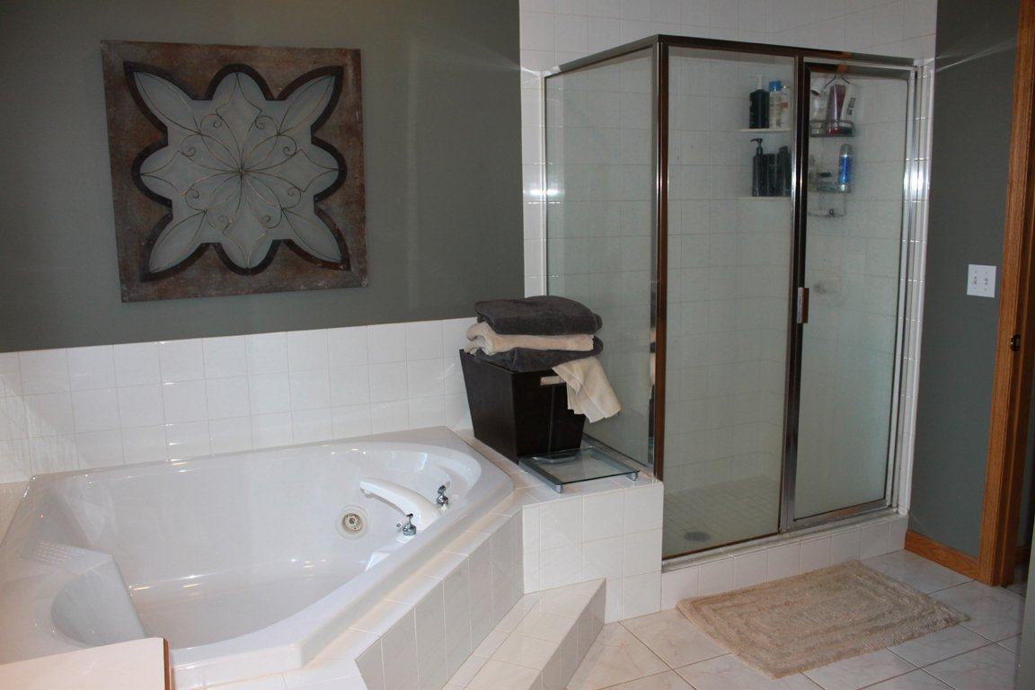 An outdated shower door and too-large tub kept this bathroom stuck in the 1990s.