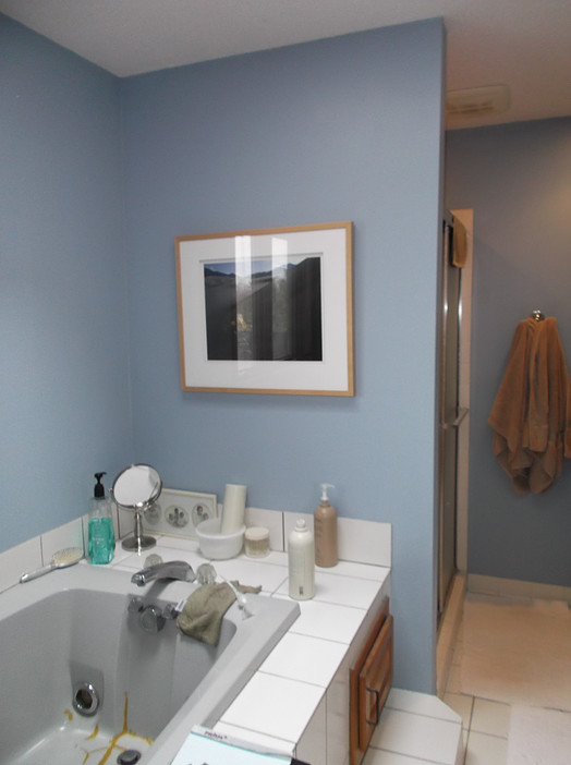 Powder blue walls paired with a gray tub, white tiles, and oak trim made for an overwhelming color palette.