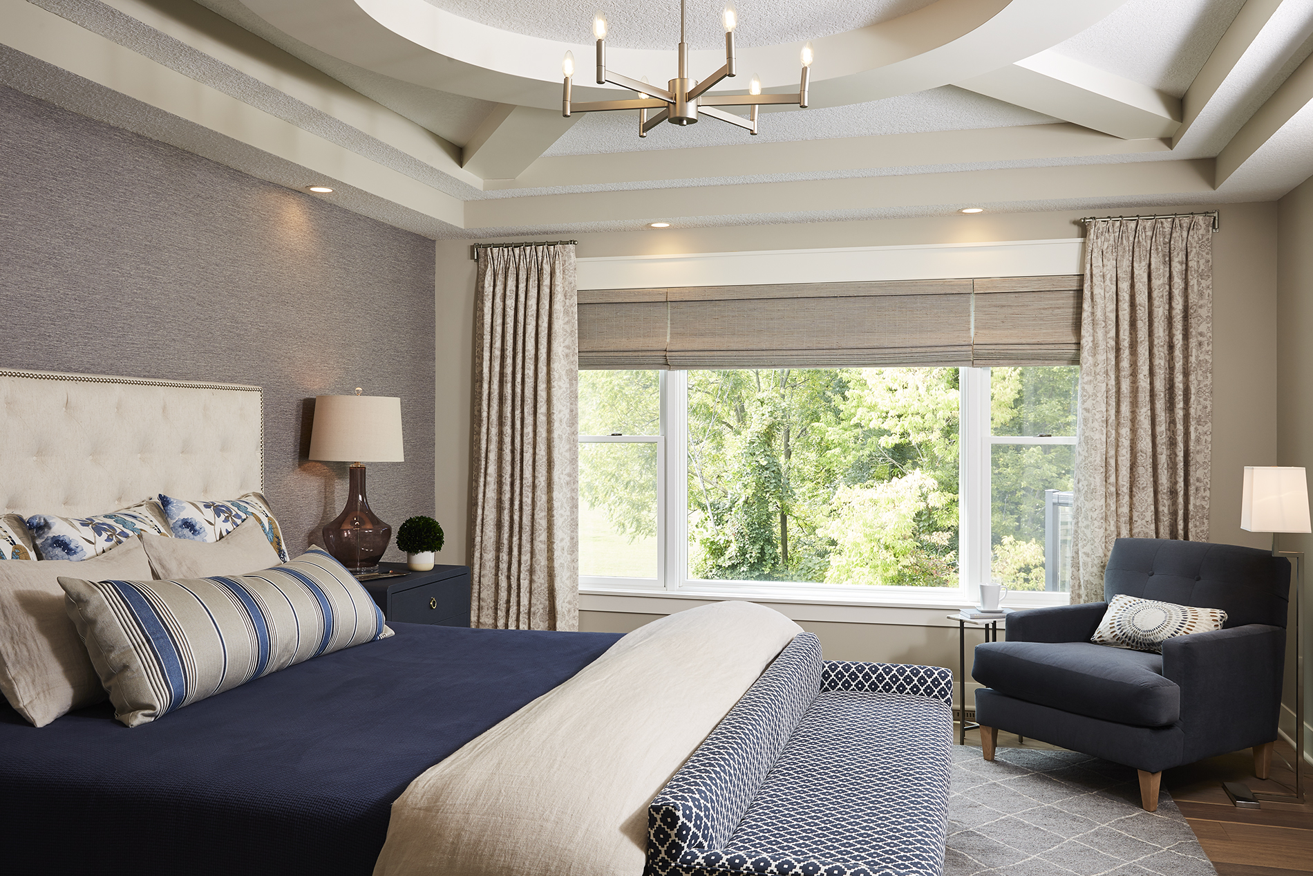 In this master bedroom, shades of blue combine with soft beige and grey to create a colorful, yet calming neutral space that wows. / Design by Sneak Peek Design