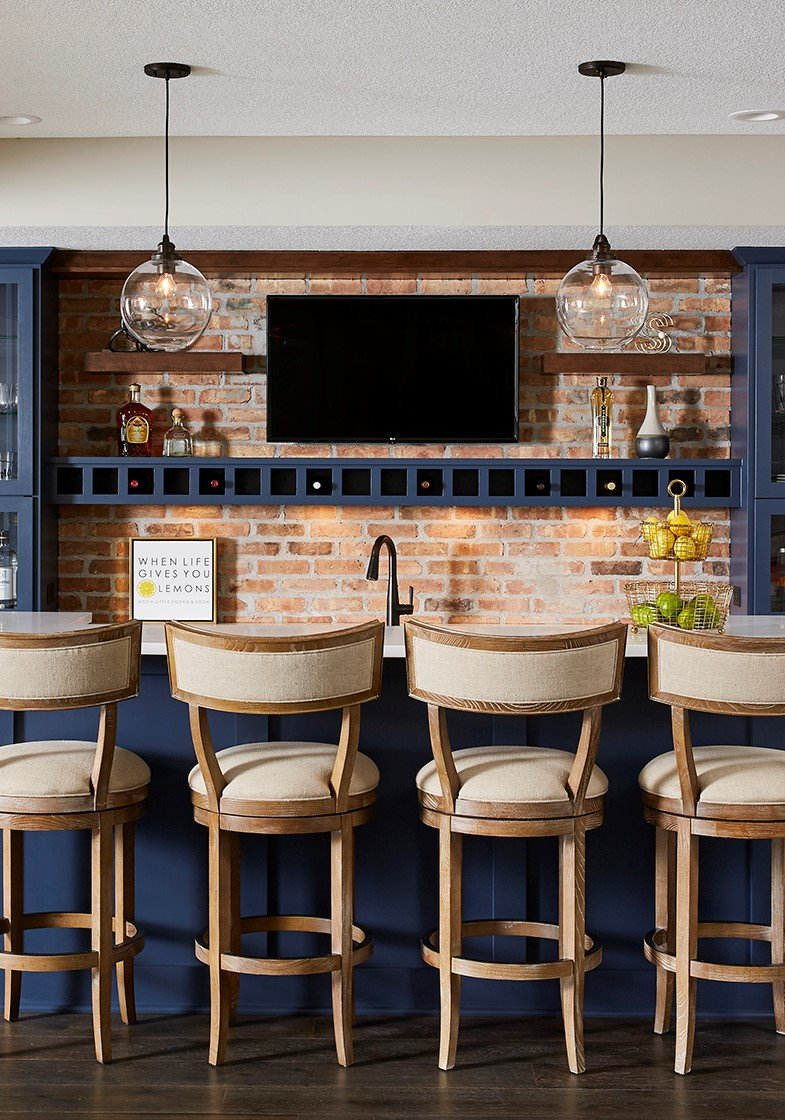 A basement bar gets an infusion of personality with a pop of blue similar to Classic Blue; paired with an exposed brick wall, it feels both modern and traditional at once. / Design by Sneak Peek Design