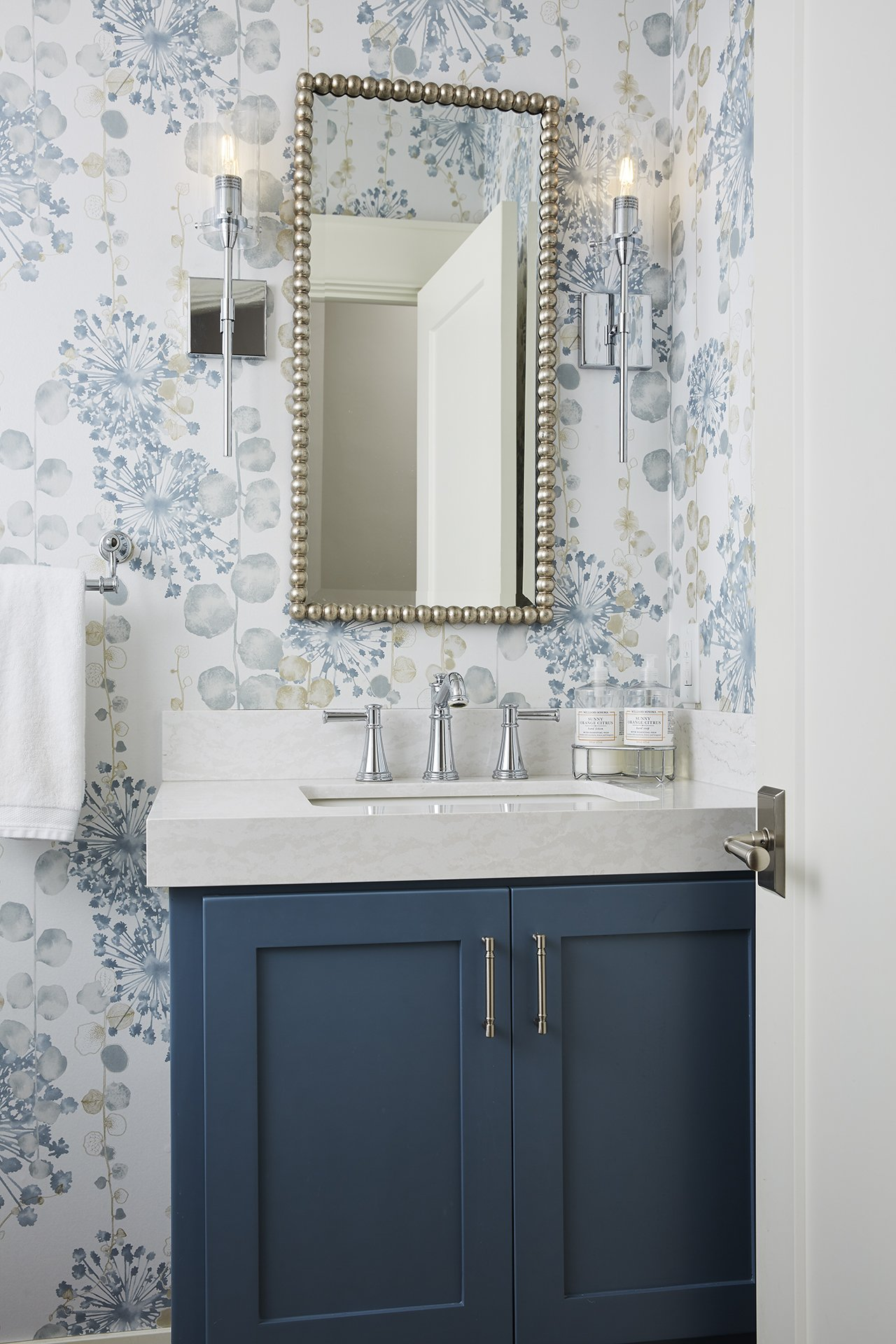 A chic bathroom pairs a soft floral wallpaper with a bold blue vanity for a stunning and fresh aesthetic that is both stylish and functional. / Design by Sneak Peek Design