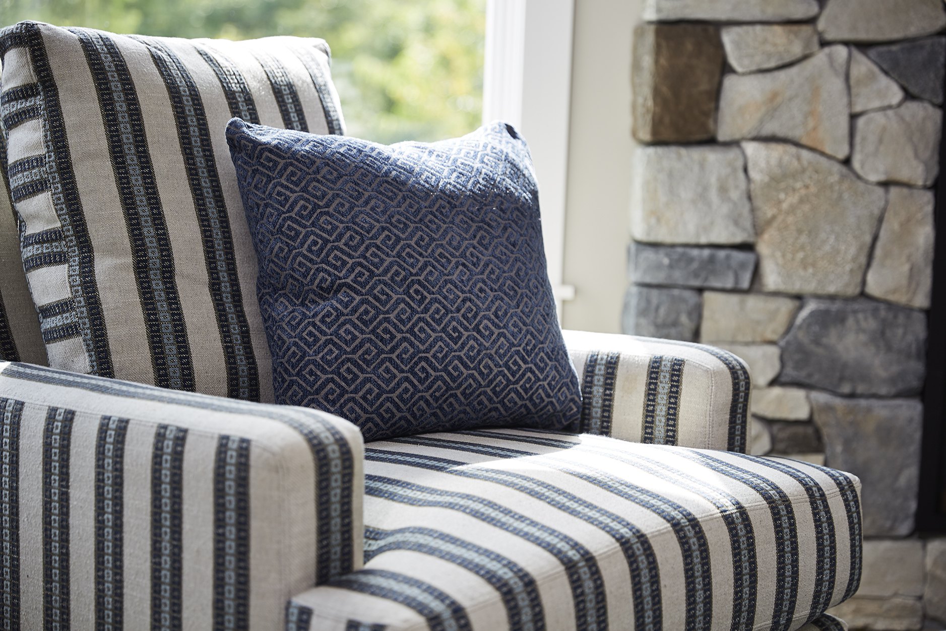 Layers of blues in various patterns make this accent chair pop next to a luxurious stone fireplace. / Design by Sneak Peek Design