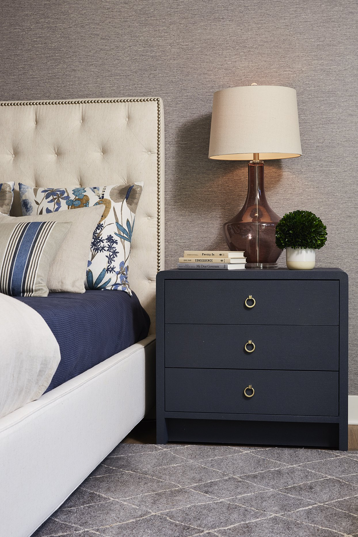 In this master bedroom, we opted for a deep blue color scheme layered in both traditionally masculine and feminine patterns, with stripes and florals paired together for a curated bedroom look. / Design by Sneak Peek Design